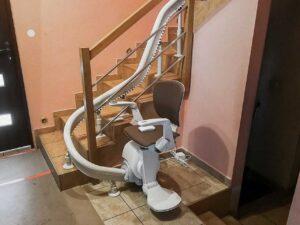 transport chorego męża po schodach zakręcających na piętro domu